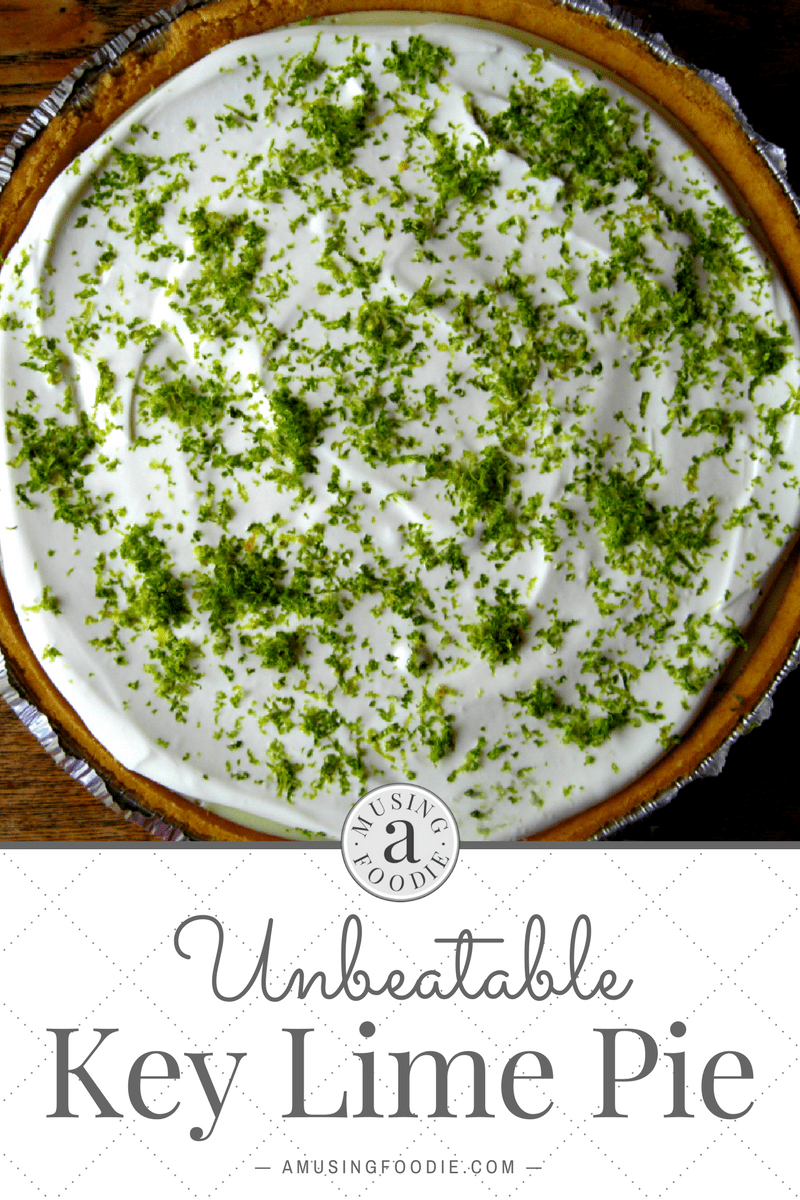 Fresh lime zest on top of homemade key lime pie with a sour cream topping and graham cracker crust.