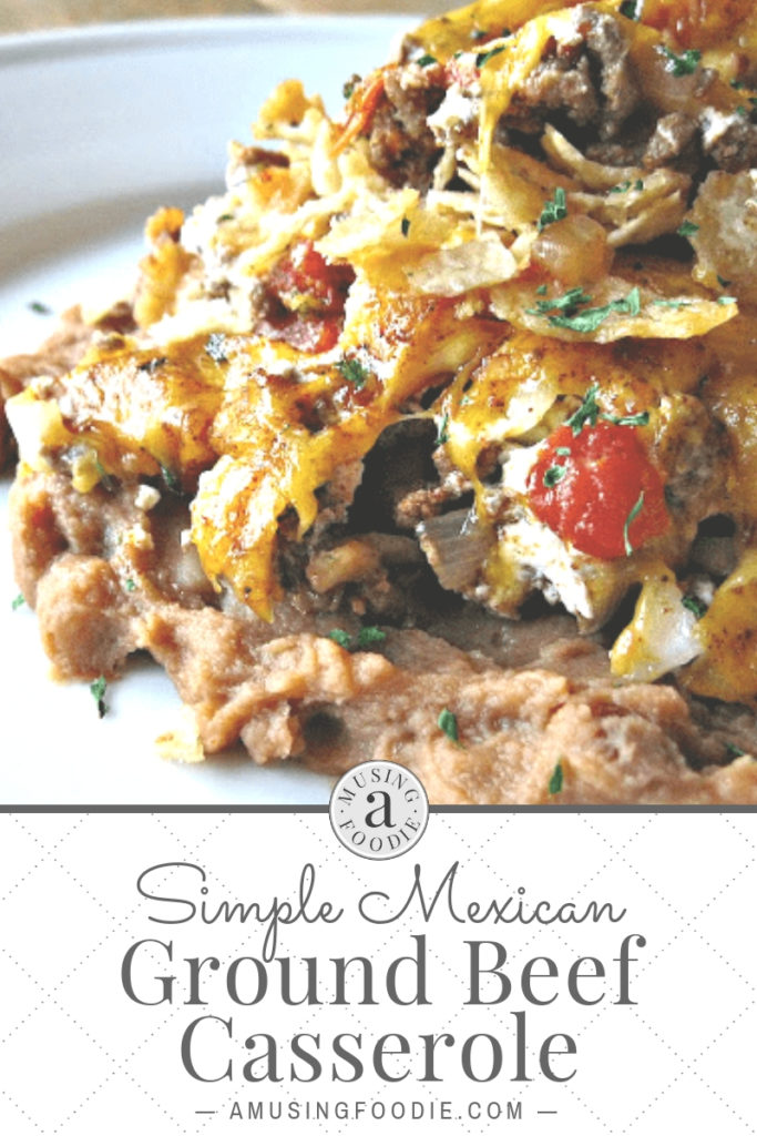 Serving of Mexican ground beef casserole, with layers of crunch tortilla chips, diced tomato, ground beef, onions and garlic, on top of warm refried beans.