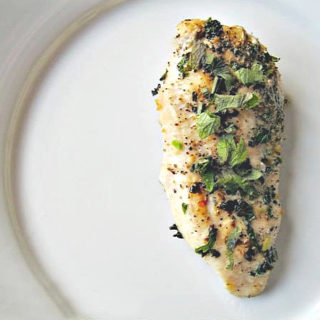 Seared lemon balm chicken on a white plate.