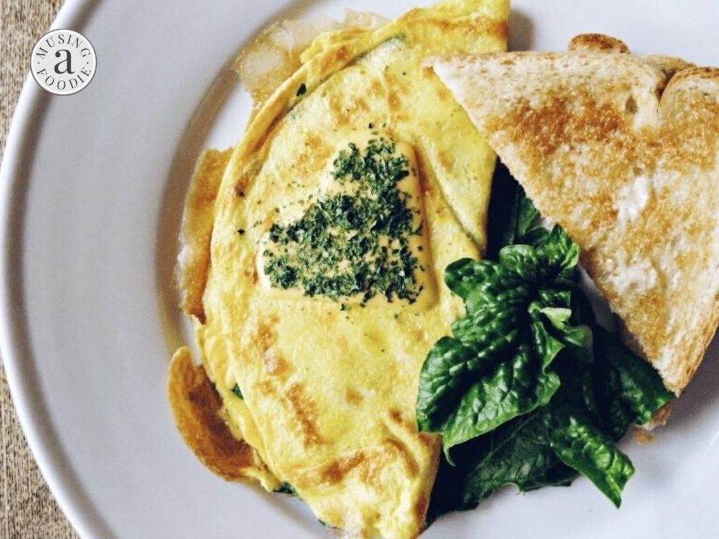 Omelette made with cheese, spinach and lump crab meat and served with buttered toast.