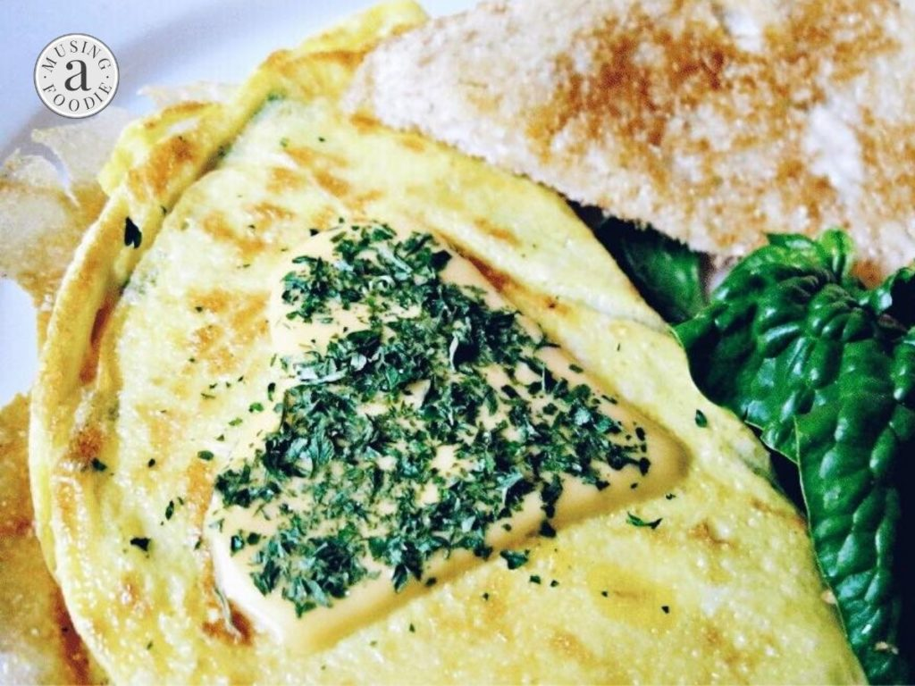 Close up of an omelette made with cheese, spinach and lump crab meat and served with buttered toast.