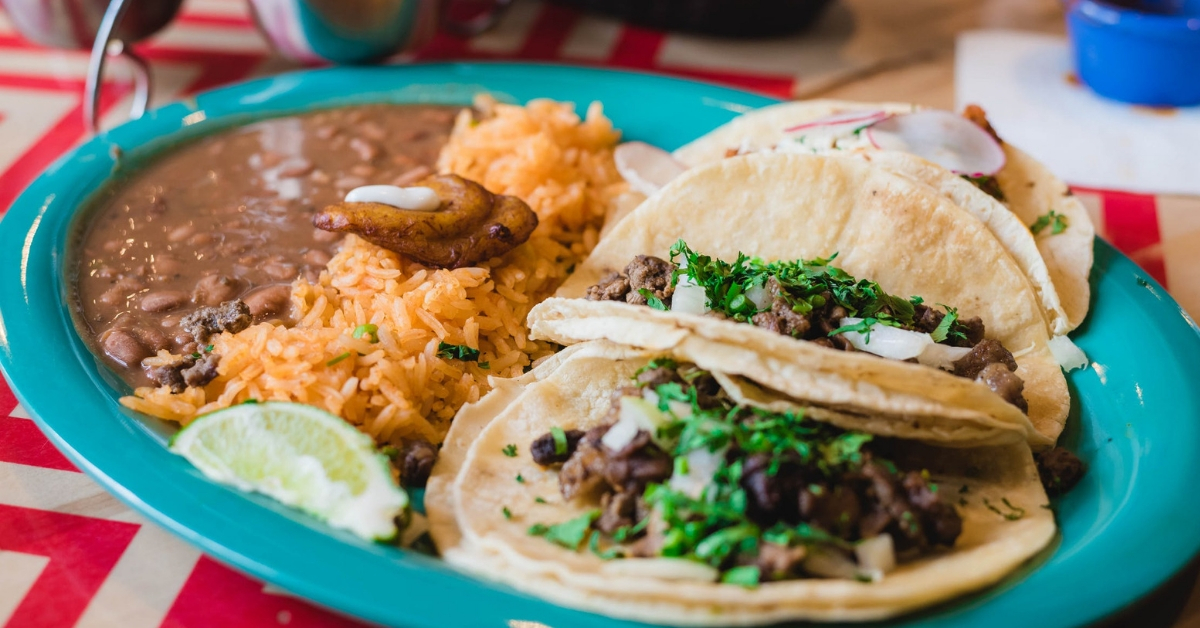 Plate with refried beans, tacos and rice.