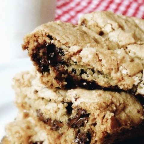 Stack of chocolate chip cookie bars with a glass of milk