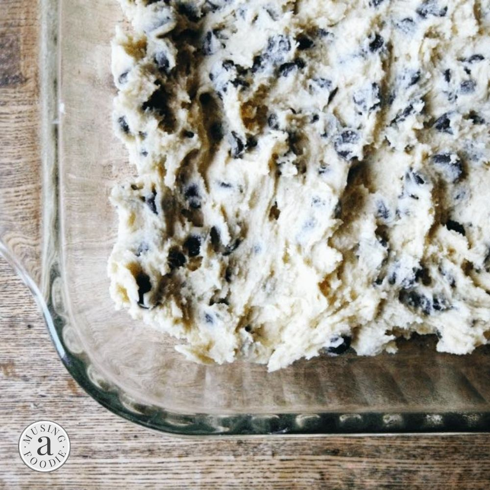 Chocolate chip cookie bar dough pressed into a buttered glass baking dish