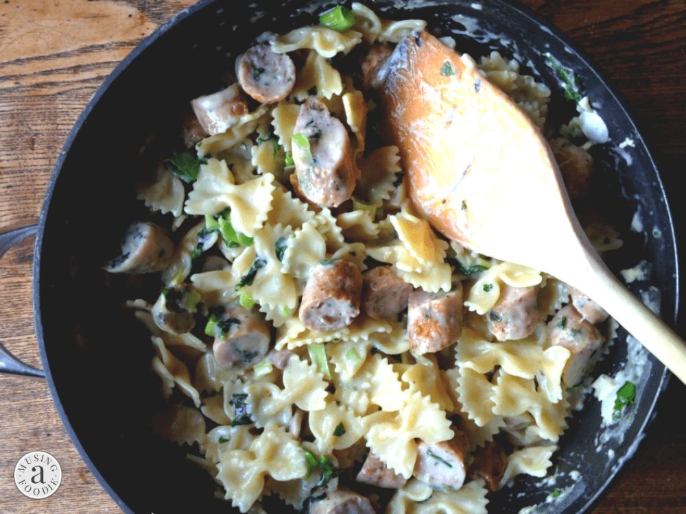 Skillet with faralle pasta cooked in a garlic cream sauce and served with seared chicken sausage.