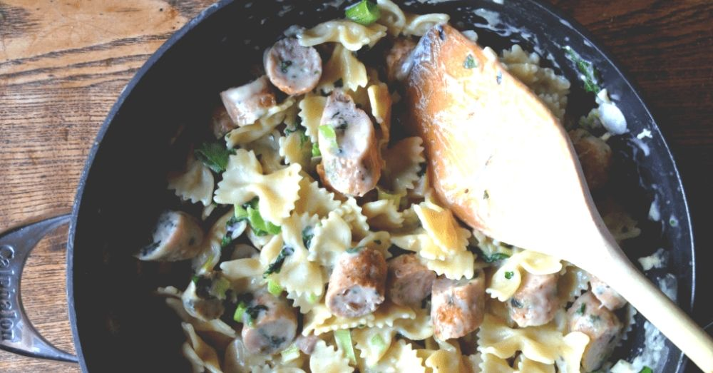 Farfalle with garlic cream sauce and seared chicken sausage in a skillet.