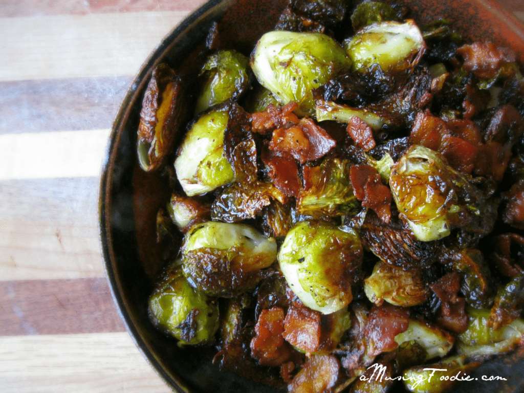 Roasted brussels sprouts with bacon in a brown ceramic bowl on a wooden cutting board.