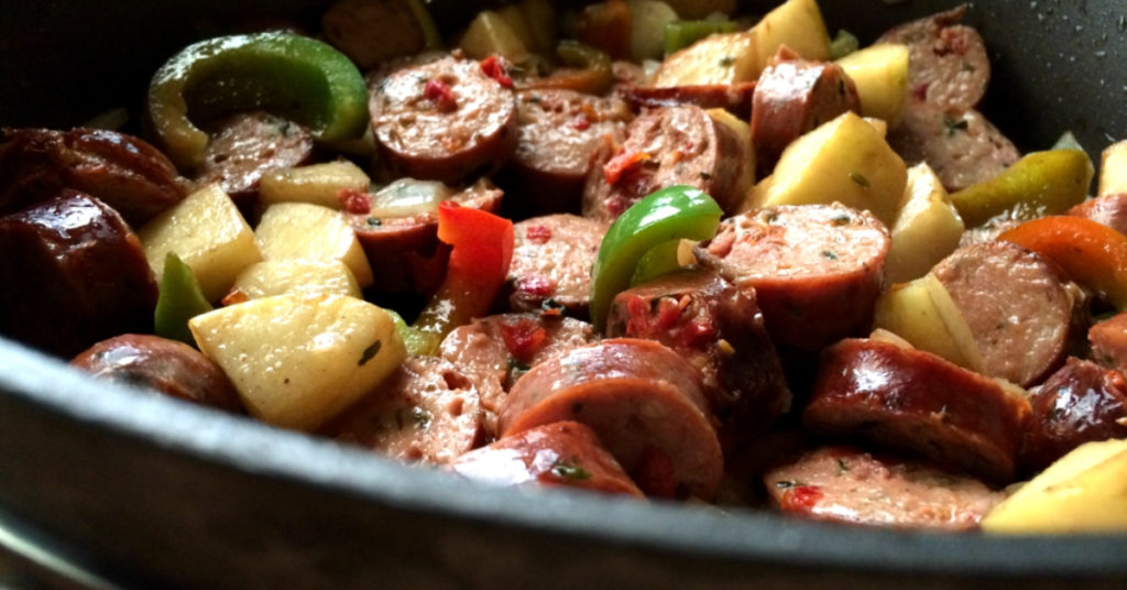 Sauteed chicken sausage, apples and peppers in a pan.