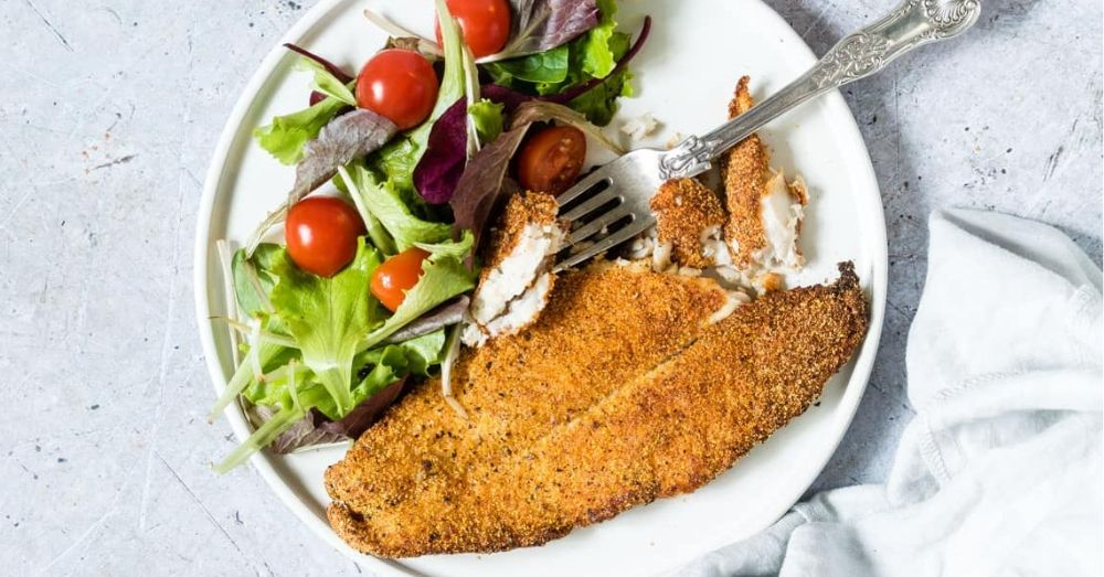 Golden crispy air fryer catfish plated with a side salad.