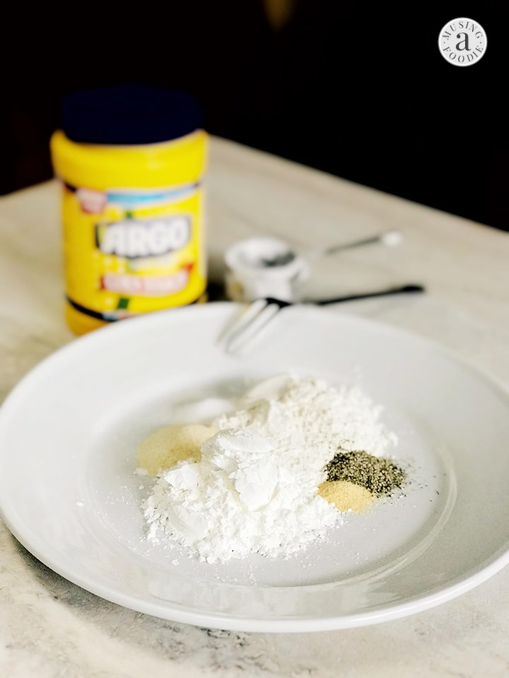 Corn starch, flour, salt, pepper, onion powder and garlic powder on a plate with Argo® Corn Starch in the background.