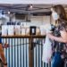 Two women standing in a coffee shop with bags of coffee behind them.